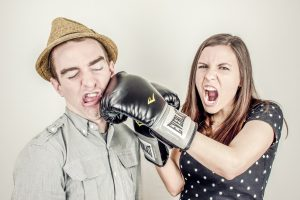 woman hitting man with a boxing glove