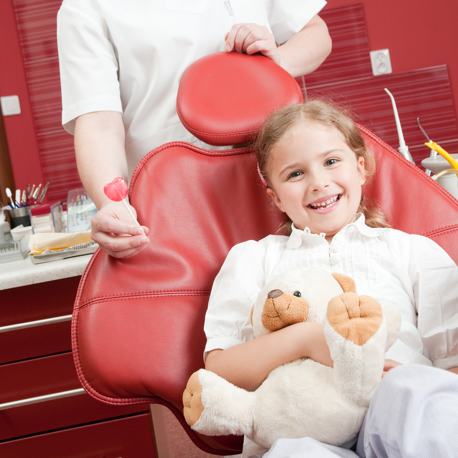 little girl smiling in a dental chair